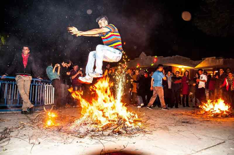 Chaharshane Suri or the Festival of Fire in Iran-Happy Iranians jumping over fire to celebrate